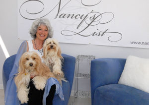 Dr. Nancy Novak with her dogs, sitting in front of Nancy's List banner